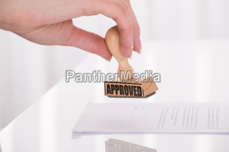 persons hand stamping approved on contract