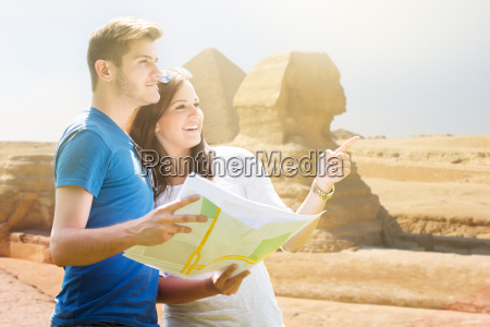 woman showing direction to man holding