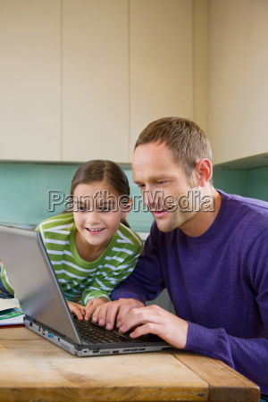 father and daughter using laptop