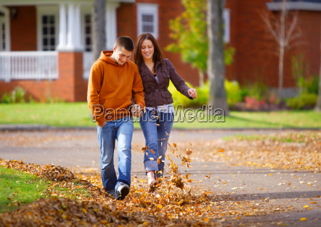 couple walking and kicking autumn leaves