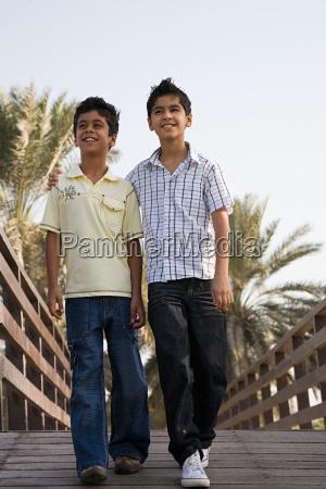 two boys walking along a bridge