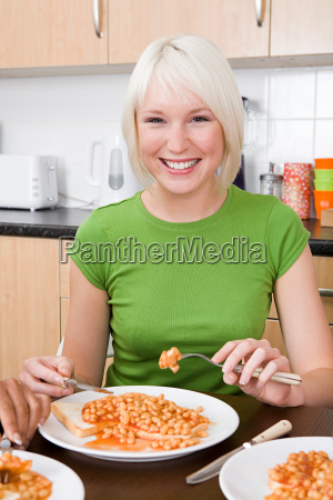 young woman eating beans on toast