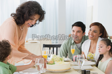 woman cutting cake with family