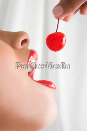 a woman holding a cherry