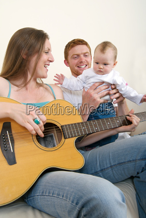 mother playing guitar for her baby