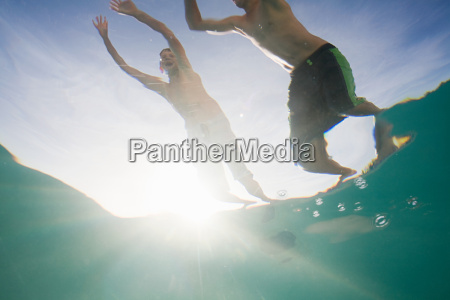 boys jumping into swimming pool
