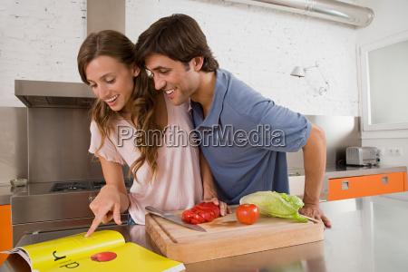 a couple reading a cookbook