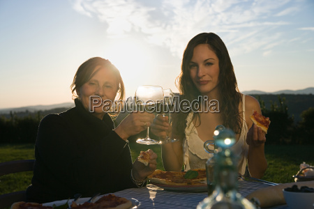 mother and daughter toasting with red