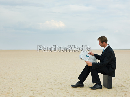 businessman reading a newspaper in the