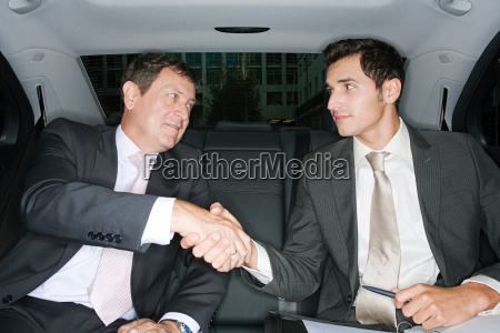 businessmen shaking hands in a car