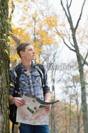 young man in forest with map