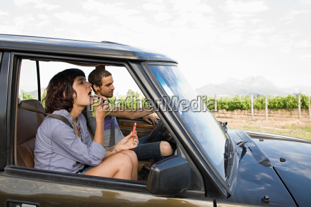 woman putting on lipstick in vehicle