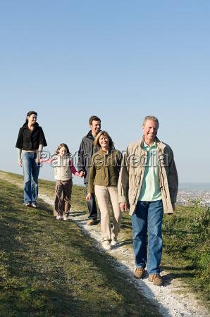 family walking on grassy hill