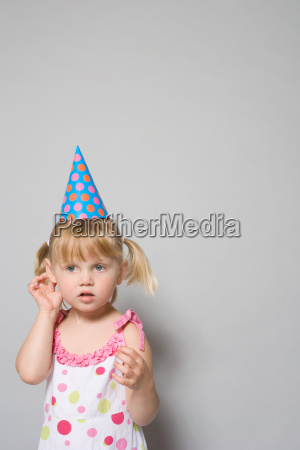 girl wearing a party hat
