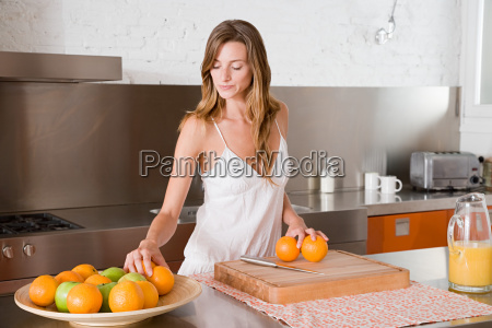 a woman making orange juice