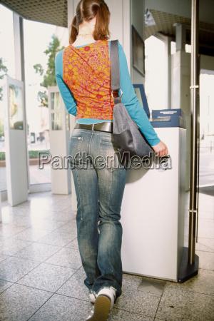 teenage girl withdrawing money