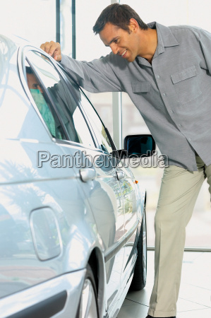man looking at car