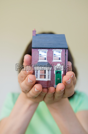 woman holding a model house