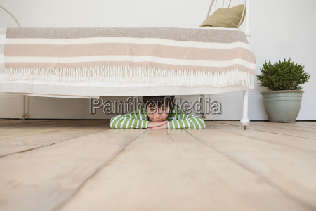 boy hiding under a bed