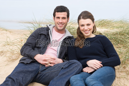 couple sitting on a sand hill