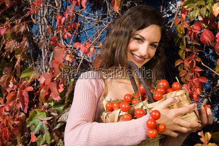 woman holding a basket of tomatoes