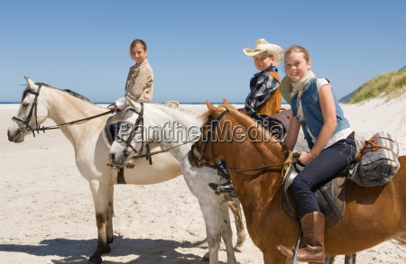 a boy and girls riding horses