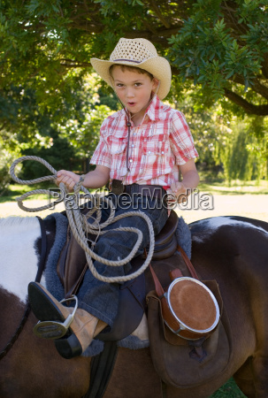 a boy riding a horse and