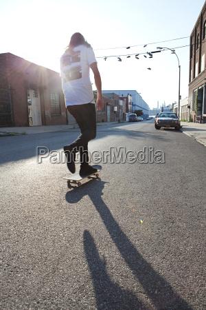 skateboarder on urban street in sunlight