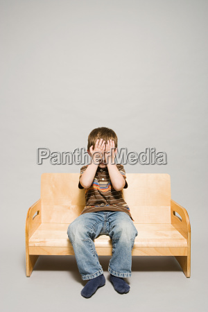 a boy covering his eyes