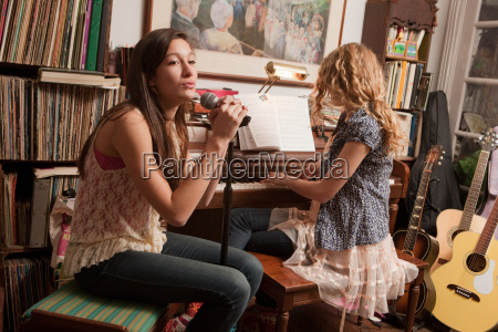 teenage girls playing piano and singing