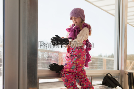 girl getting dressed in winter clothing