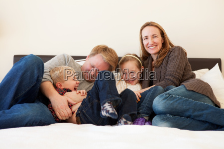 family sitting on bed portrait
