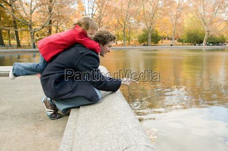 father and daughter by pond