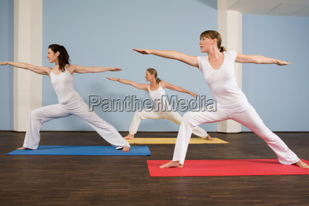 three women practising yoga