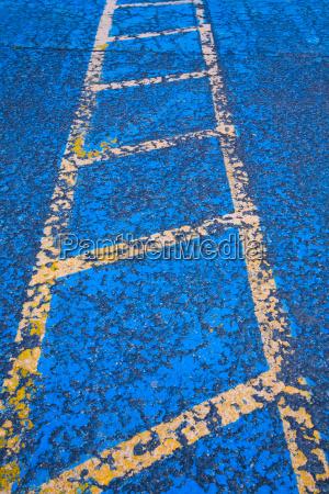 gelbe strasse auf blauem asphalt kennzeichnung