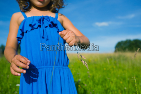 a girl holding a blade of