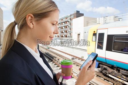 geschaeftsfrau mit kaffee und smartphone in