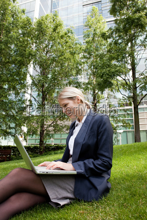 businesswoman sitting on grass and using