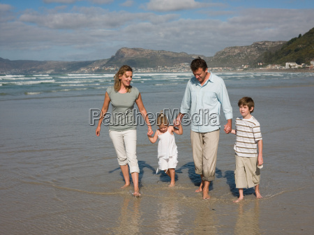 family walking in the sea