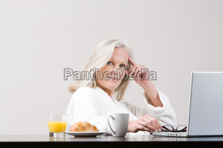 middle aged woman using laptop at