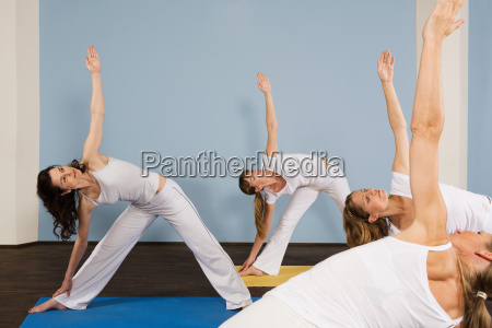 four women practising yoga