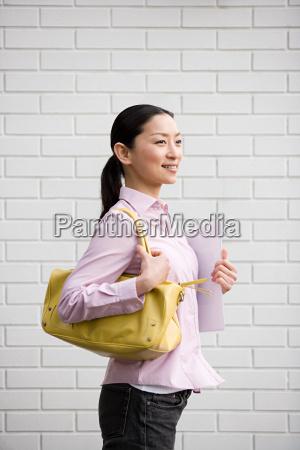 smiling woman holding a handbag