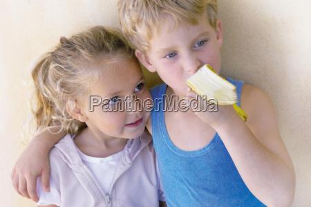 boy hugging sister and eating banana