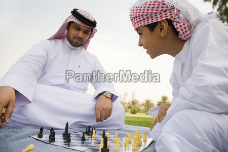 a father and son playing chess