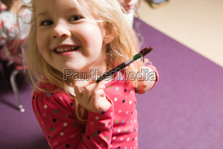 a girl holding a paintbrush