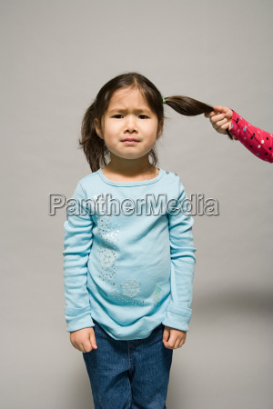 a girl having her hair pulled