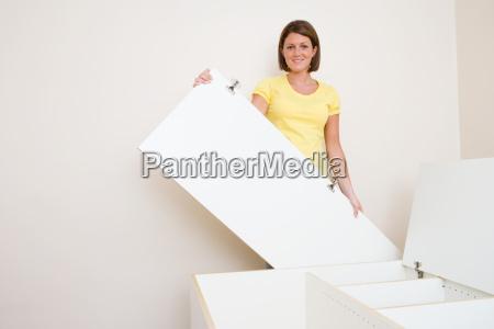 a young woman assembling a wardrobe