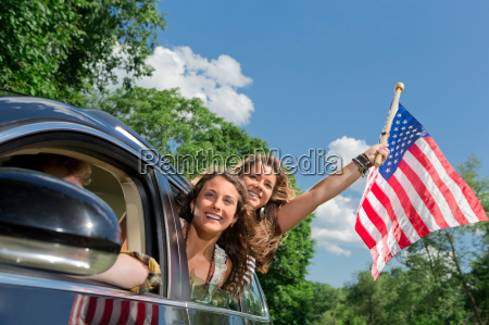 two friends leaning out of car
