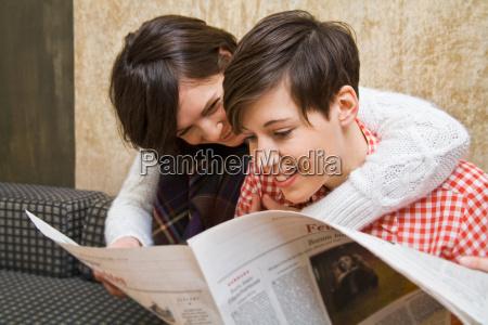 a lesbian couple reading a paper
