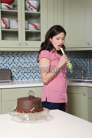 young woman eating celery watching chocolate
